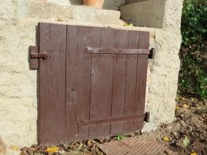 Het gerepareerde deurtje van de waterput. Hij kan nu netjes dicht