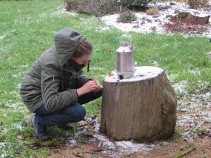 Miranda druk bezig met haar ketel op hout gestookt